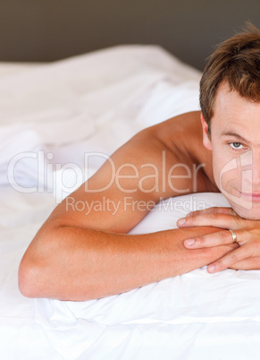 Young man relaxing in bed looking at the camera