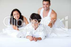 Couple and son enjoying together in bed