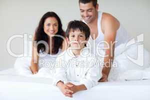 Young couple and son playing in bed