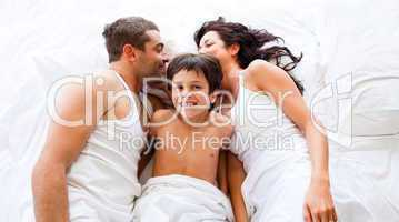 Couple and son lying in bed
