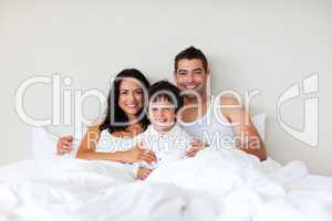 Couple and son together in bed smiling at the camera
