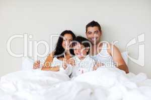 Child with thumbs up and his parents in bed
