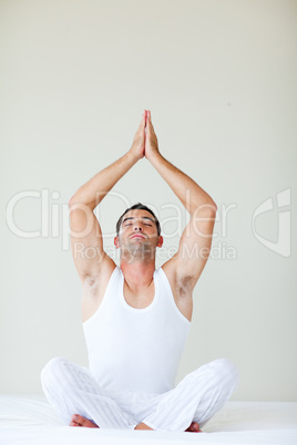 Young man doing meditation in bed