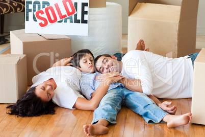 Family moving house resting on floor