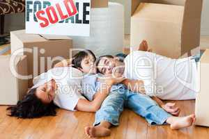 Family moving house resting on floor