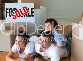 Family buying new house lying on floor