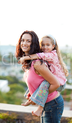Mother giving daughter piggyback ride outdoors