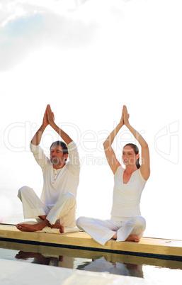 Man and woman doing yoga near the sea