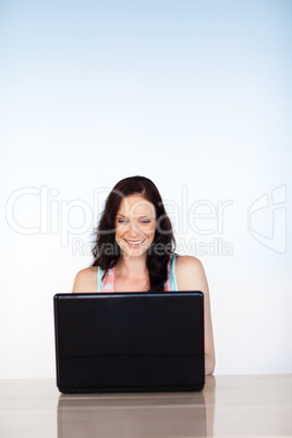 Smiling woman using her laptop with copy-space