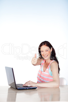 Smiling woman using a laptop with thumb up and copy-space