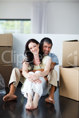 Smiling couple sitting in their new house