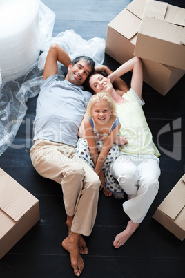 Parents and daughter on the floor with a lot of boxes