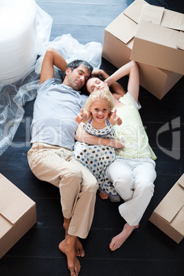 Parents and daughter on the floor with thumbs up