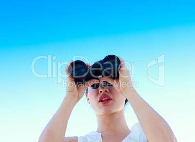 Businesswoman looking through binoculars