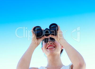 Smiling businesswoman looking through binoculars