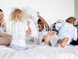 Parents and children playing with pillows on bed