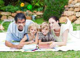 Happy family painting in a park smiling at the camera