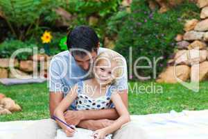 Father and daughter reading in a park