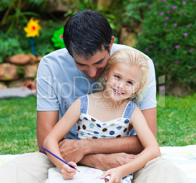 Father and daughter drawing in a park