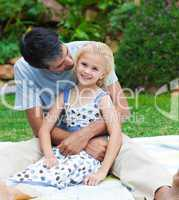 Father playing with his daughter in a garden