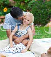 Father kissing his daughter in a garden