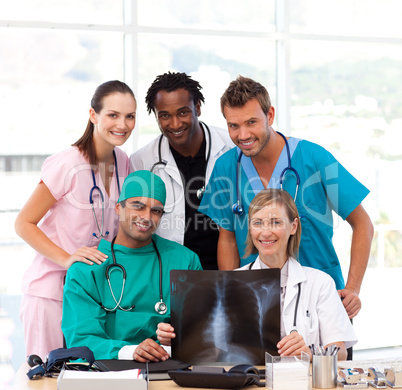 Medical team examining an X-ray and smiling at the camera