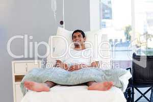 Hispanic patient in bed smiling at the camera