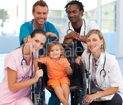 Group of doctors with a baby in a wheelchair