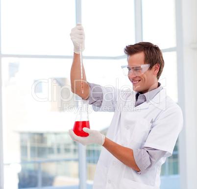 Smiling scientist examinig a test-tube