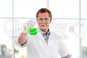 Smiling scientist examining a test-tube
