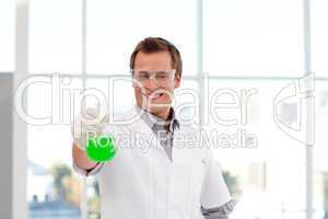 Smiling scientist examining a chemical test-tube