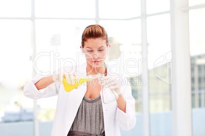 Blond female scientist examinig a test-tube