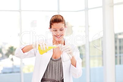 Smiling female scientist examinig a test-tube