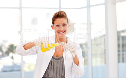 Attractive scientist examining a test-tube smiling at the camera