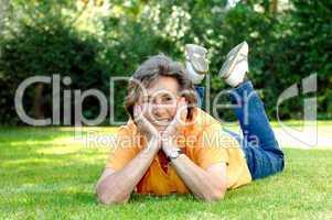 Ältere Frau, entspannt auf einer Wiese liegend