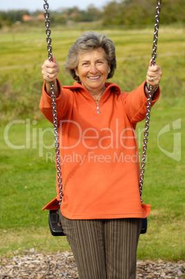 Seniorin auf einem Spielplatz