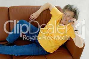 Seniorin auf Ledercouch telefoniert
