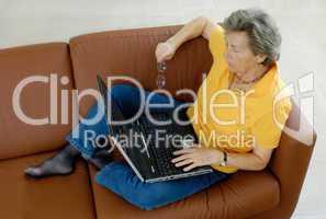 Seniorin mit Laptop auf Couch