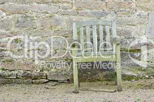 Alter Stuhl vor Natursteinmauer