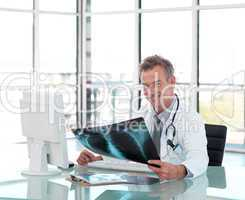 Middle aged doctor working at his Desk