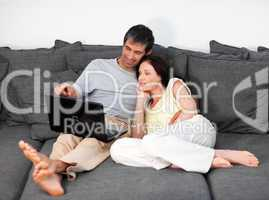 Couple laying on couch with laptop