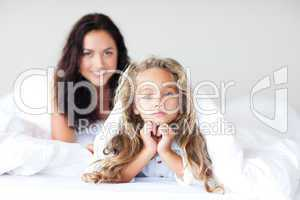 Mother and daugther embracing on bed