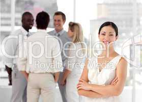 Attracive and confident business woman in front of a group of associates smiling
