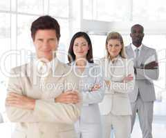 Business man with arms folded in front of Business Team