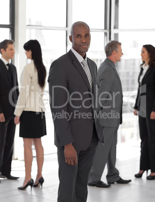 business leader looking at camera in front of team