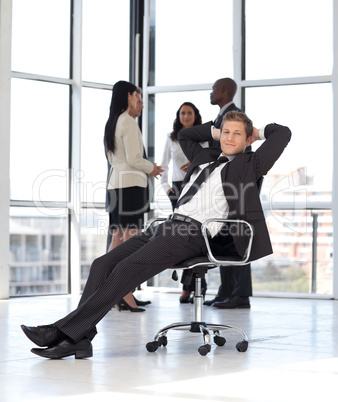 manager relaxing in office with team in background