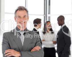Senior Businessman with team in Background