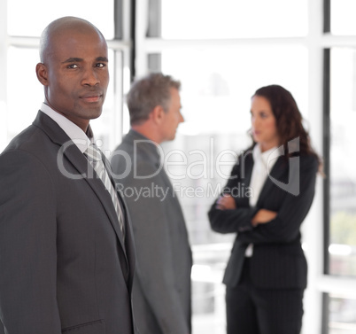 Serious business leader looking at camera in front of team