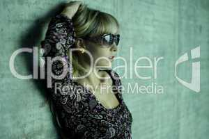 young blonde with sunglasses and one hand in her hair