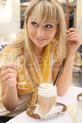 young blond woman in a cafe with latte macchiato